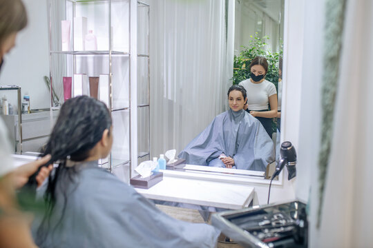 Hair stylist working in a beauty salon in pandemic times