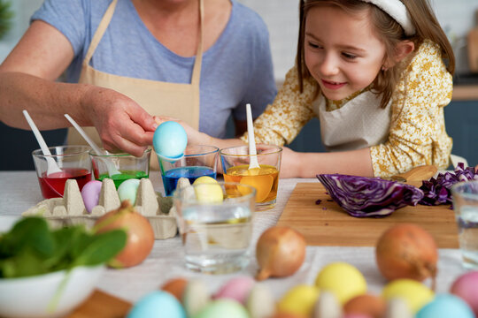 Little girl with grandmother dyeing Easter eggs