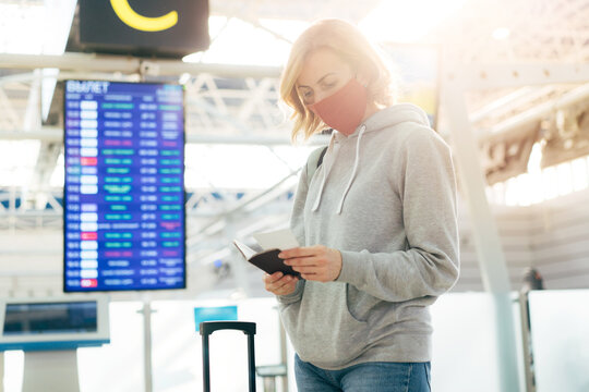 A woman in a medical protective mask stands at the airport near the departure board and checks her passport and ticket.