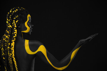 Fototapeta Face art. Girl showing on copy space with hand Woman with black and yellow body paint. Young african girl with colorful bodypaint. An amazing afro american model with makeup. obraz