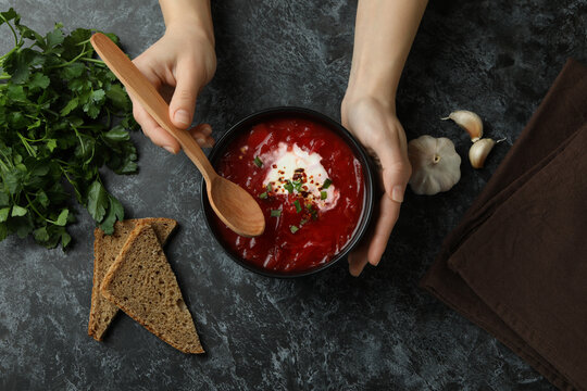 Woman eat borscht on black smokey table with ingredients, top view