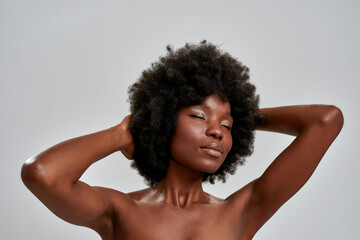 Portrait of sensual african american female model with afro hair and perfect glowing skin posing...