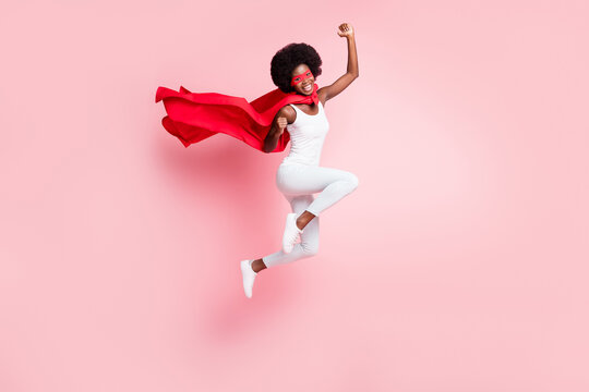 Full length body size view of active cheery girl jumping rejoicing wearing hero costume isolated on pink pastel color background