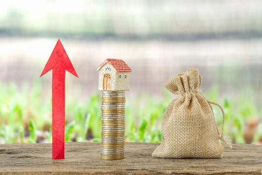 Money coin stack with wooden house.Property investment and house mortgage financial concept,.arrow of the diagram grows up on wooden with coins stack,
