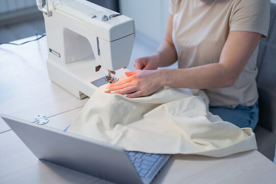 Caucasian woman teaches how to sew on a sewing machine from video. Distance education