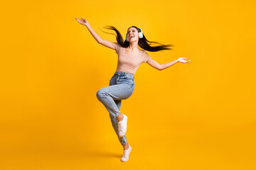 Full size photo of young happy crazy smiling cheerful girl dancing in headphones with flying hair...