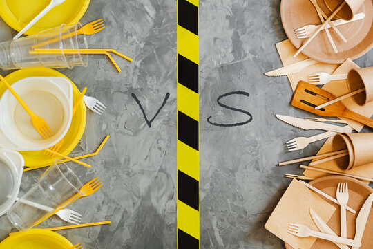 Top above  view photo of white and yellow plastic and wooden  utensils compared on grey background.