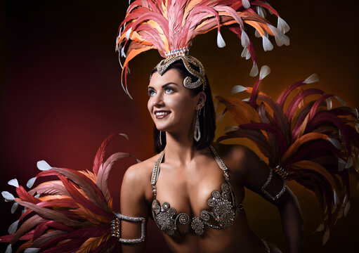 Attractive female cabaret dancer in carnival costume with red and pink feathers.