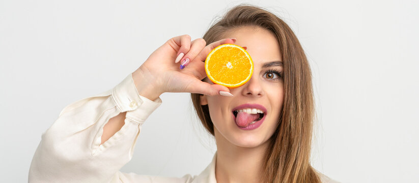 Portrait of a cheerful caucasian young woman covering eye with an orange slice and stick out tongue wears white shirt against a white background