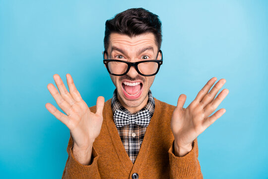 Photo of crazy angry young man scream loud raise palms wear plaid bow tie isolated on blue color background