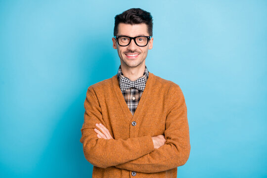 Photo of cheerful funny young man hand wear brown cardigan spectacles arms crossed isolated blue color background