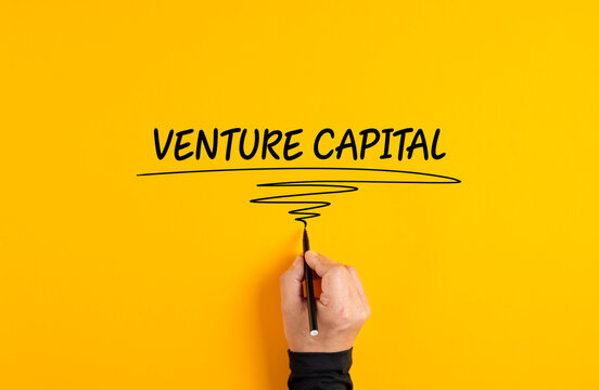 Male hand writing venture capital on yellow background.