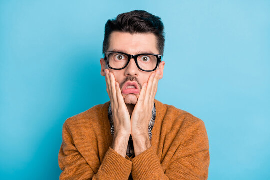 Photo of young man amazed shocked surprised stupor hands touch cheeks isolated over blue color background