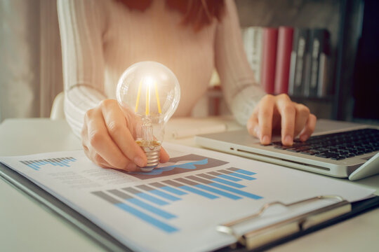 Digital Composite Image Of Woman Holding Illuminated Light Bulb While Using Laptop On Table