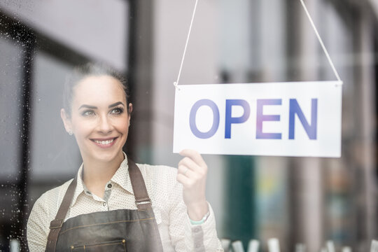 Smiling beautiful waitress turning the sign open  on a restaurant or a bar