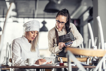 Obraz Female chef and waitress sit over bills calculating after hours in a restaurant - fototapety do salonu