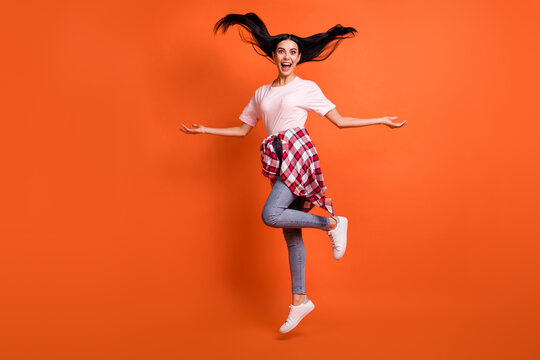 Full size profile portrait of adorable person jump high arms sides open mouth isolated on orange color background