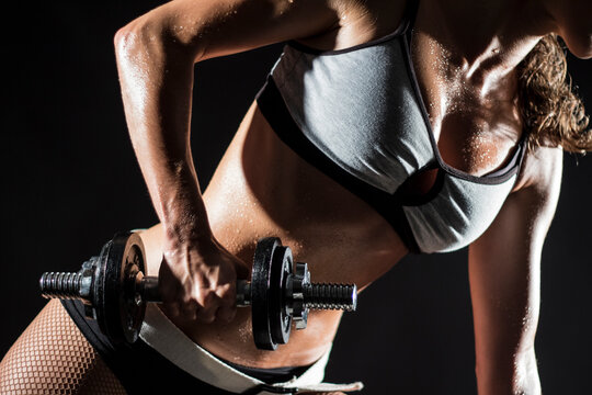 Midsection Of Woman Exercising Against Black Background