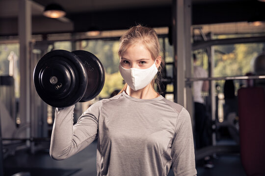 female athlete with a corona mask is training with a dumbell looking in the camera