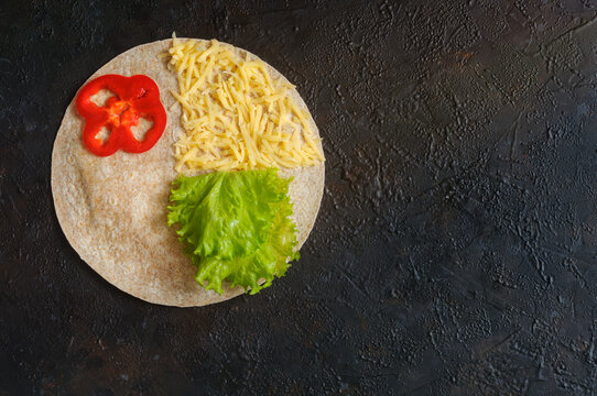 Homemade whole wheat tortilla with cheese and vegetables. Flat lay with copy space on dark background