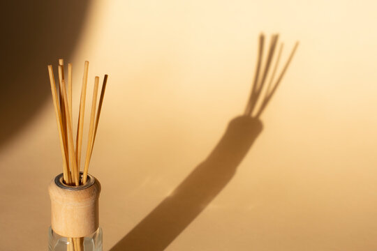 aroma rattan sticks for scenting the room and the shadow on a beige background