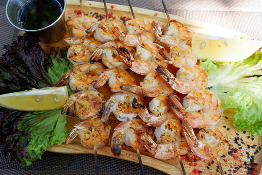 King prawns on a skewer. Seafood on a wooden board with watercress salad, lemon and sauce