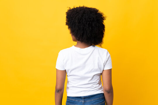 Young African American woman isolated on yellow background in back position and looking side