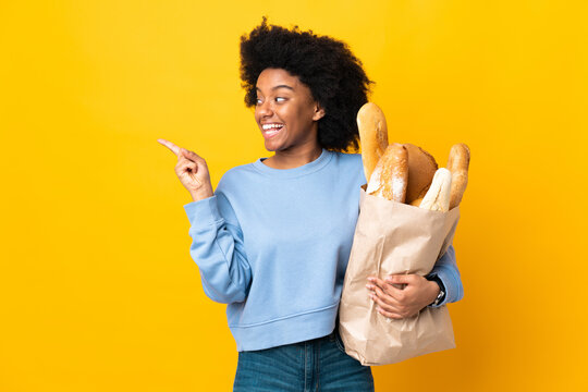 Young African American woman buying something bread isolated on yellow background intending to realizes the solution while lifting a finger up