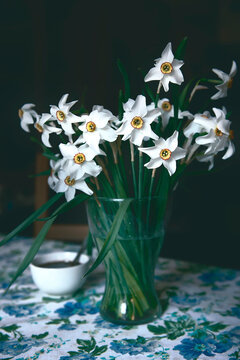 a vase of daffodils on the table.the decor of a country house,the photo was taken in daylight and stylized as a photo from a film camera.soft focus,smooth transitions of the chiaroscuro pattern.