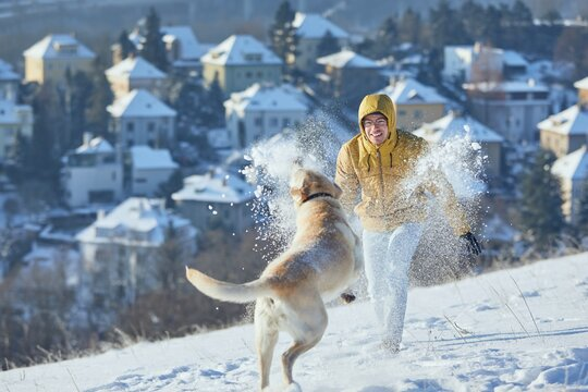Young man with dog in winter. Pet owner with his labrador retriever playing in snow against city. Prague, Czech Republic