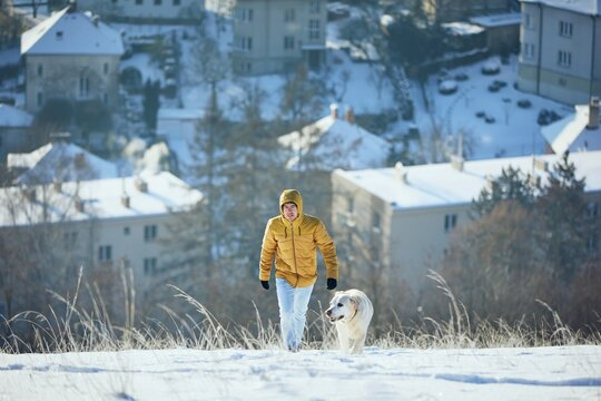 Happy young man with dog in winter. Pet owner with his labrador retriever walking in snow against city. Prague, Czech Republic