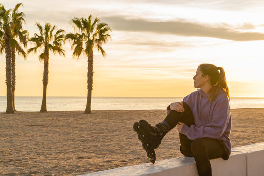 Young beautiful rollerskating woman sitting near the beach at sunset.Healthy lifestyle , active and fitness concept with copy space.