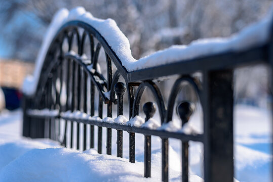 A snow-covered black forged fence made of thick metal profiles is positioned diagonally in the frame. Sunny frosty day in the park. Selective focus.