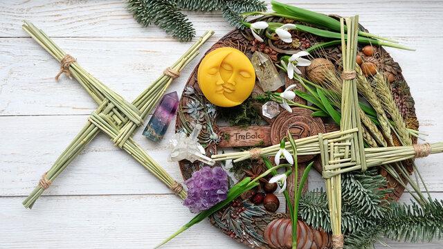 Winter altar for Imbolc sabbath. spring pagan holiday ritual. Brigid's cross, candle, wheel of the year, snowdrops, sun and moon symbol - items of Imbolc holiday, spring equinox. flat lay