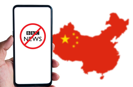 Man holds smartphone with logo of BBC News inside red circle with banned icon against the map of China in the background. Chinese Authorities recently banned BBC World News broadcast in China.