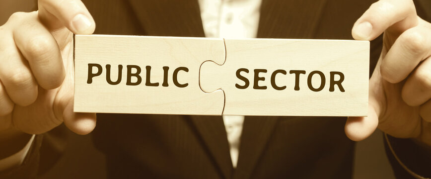 Businessman puts together wooden puzzles with the words Public sector. Enterprises, organizations and institutions owned and operated by state bodies. Business concept