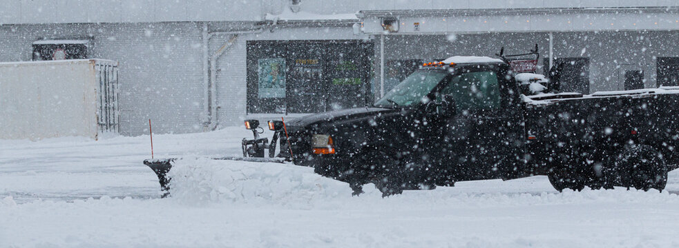 Private contractor plowing parking lot during a blizzard