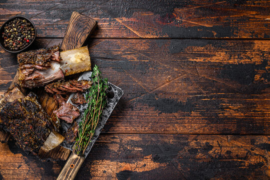 BBQ short chuck beef ribs with herbs and meat cleaver. Dark wooden background. Top view. Copy space