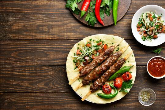 Turkish Adana Kebab with fresh vegetables on flatbread