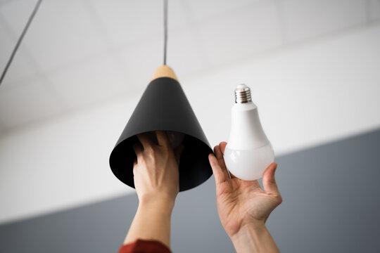 Woman Changing Broken Light Bulb