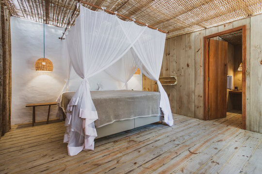 Modern luxury summer holiday or vacation wooden beach house bedroom interior with rustic canopy bed, bedside table and straw chandelir.