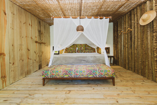 Modern luxury summer holiday or vacation wooden beach house bedroom interior with rustic canopy bed, sofa and straw chandelier. Detail of a hanging hat on the wall.