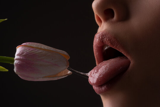 Oral sex, orgasm, blowjob, licking flower. Girl lips with tulips. Sensual sexy female mouth and spring flowers.