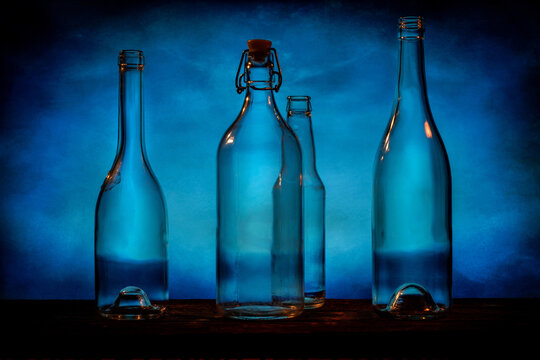 Four transparent glass bottles on a barn wood table in front of a blue background