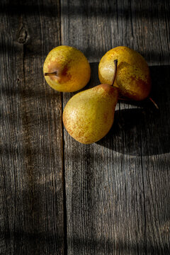 Three yellow pears on a barn wood plank table with shadows from the sun
