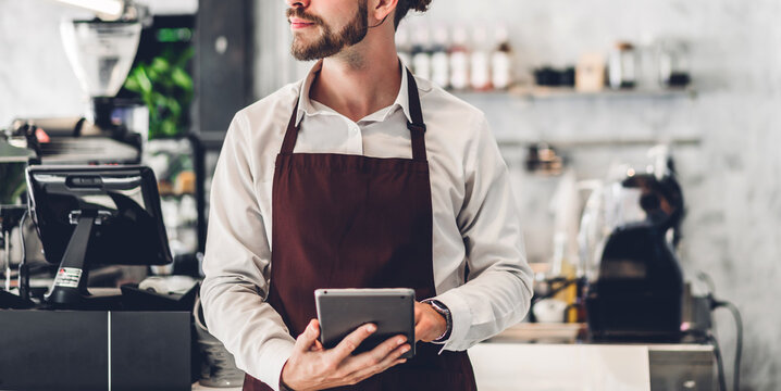 Portrait of barista man small business owner standing with tablet computer and receive order from customer in the cafe or coffee shop in a cafe
