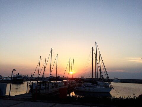 Silhouette Of Boats Moored At Harbor