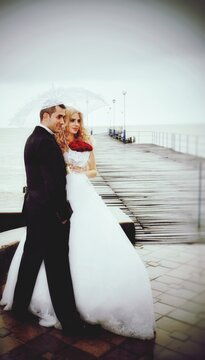 Couple Standing On Pier Against Sky