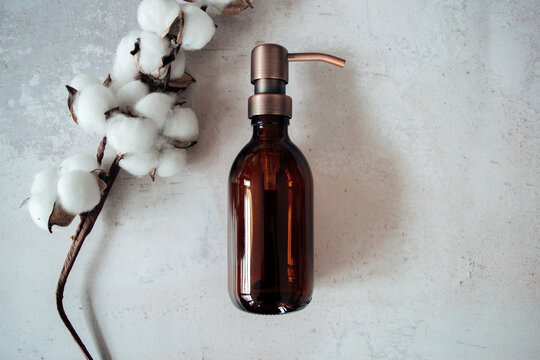 Amber glass shampoo or soap bottle dispenser with a copper steel pump against a luxury stone background. Organic spa product with cotton.