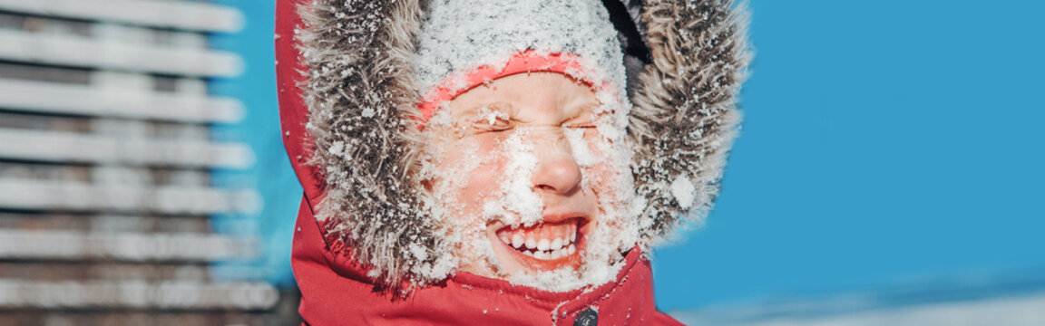 Funny smiling girl in red jacket squinting eyes from bright sun. Happy kid with snow on face at cold winter sunny day. Winter seasonal outdoors fun activity for children. Web banner header.